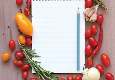 A notepad surrounded by vegetables