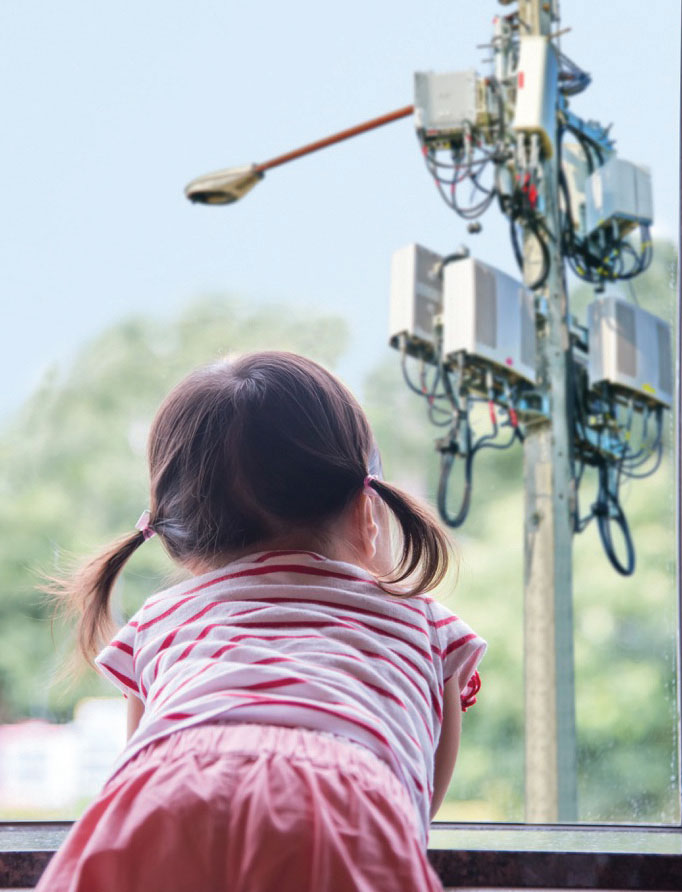 child looking out window at nearby cell tower