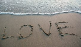 Love written in sand by the ocean
