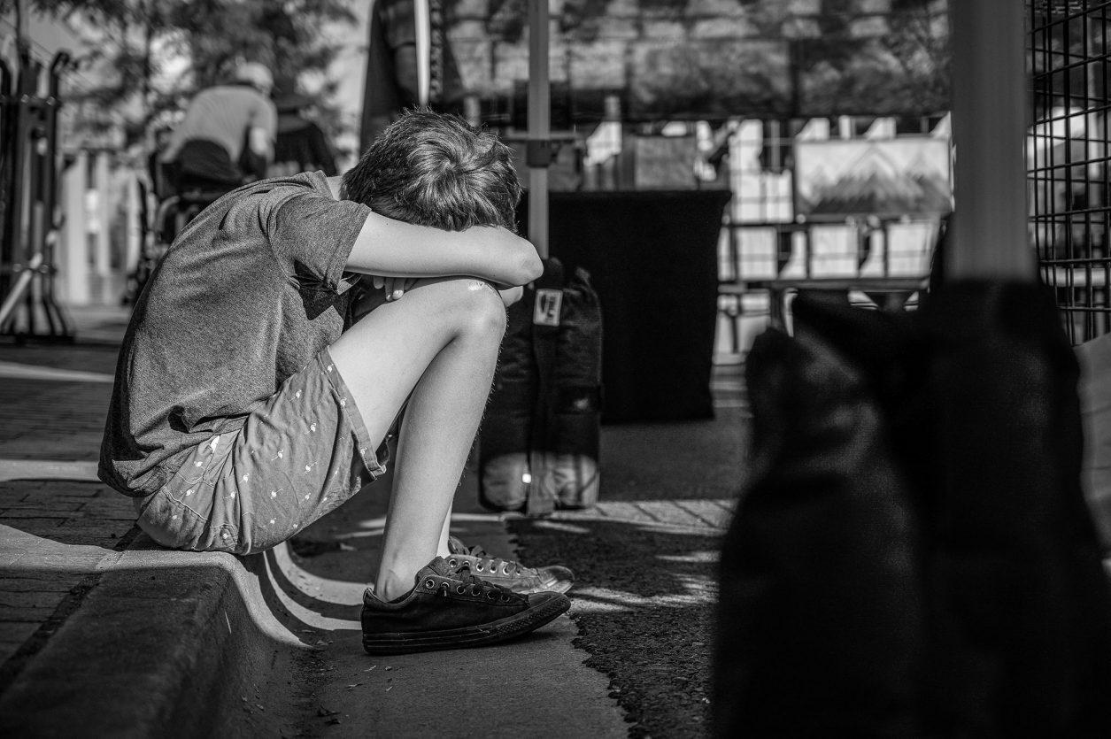 child sitting on curb