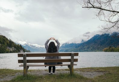woman sitting on park bench looking at mountain view