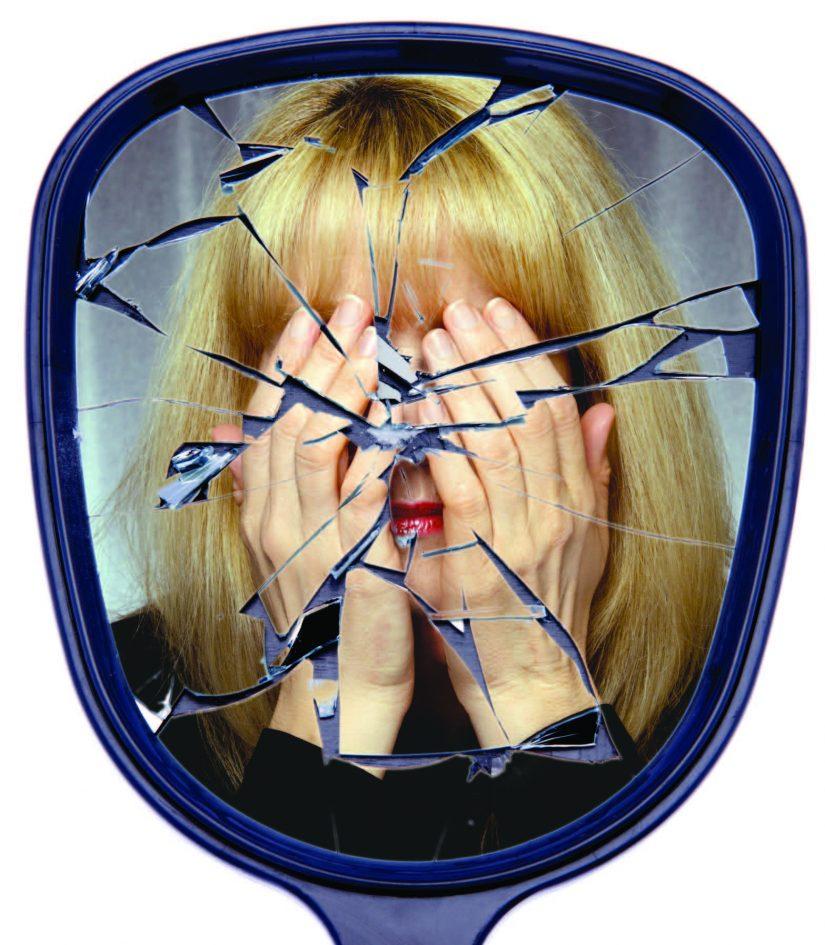 someone looking into broken mirror