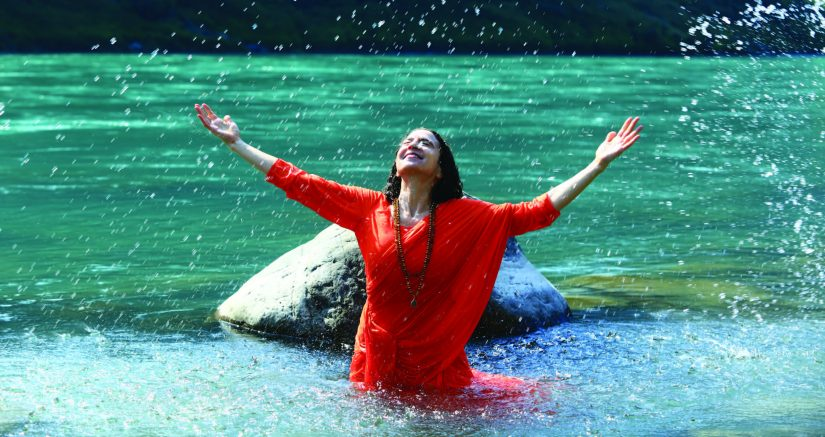 person in water with raised arms to sky